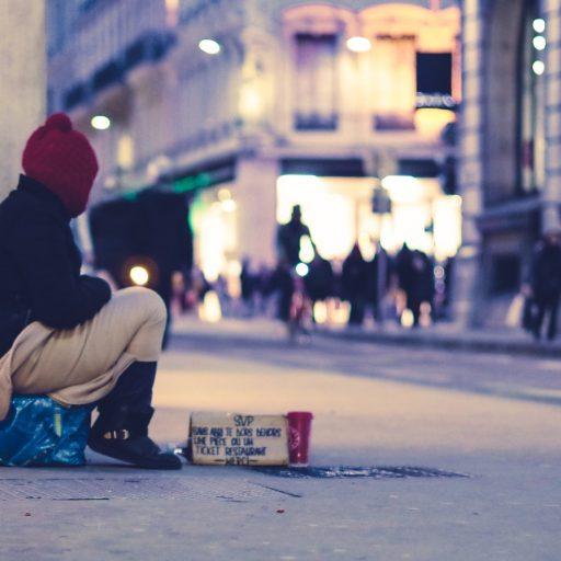 Obdachlose Person sitzt eingehüllt in eine Decke auf einem Platz in einer Stadt. Es ist Abend und vor ihr steht ein Pappbecher um Spenden zu sammeln.