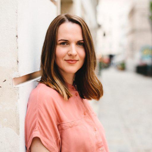 Stefanie Summerauer, Gründerin von Visionistas lehnt an einer Hauswand und blickt in die Kamera.