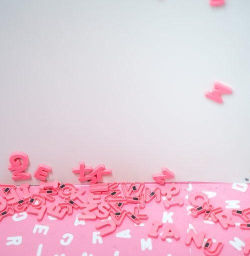 Eine Buchstabentafel aus der alle rosaroten Buchstaben rausgefallen sind