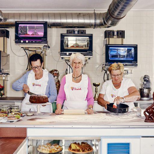 Drei Frauen stehen hinter einer Theke und backen Kuchen.