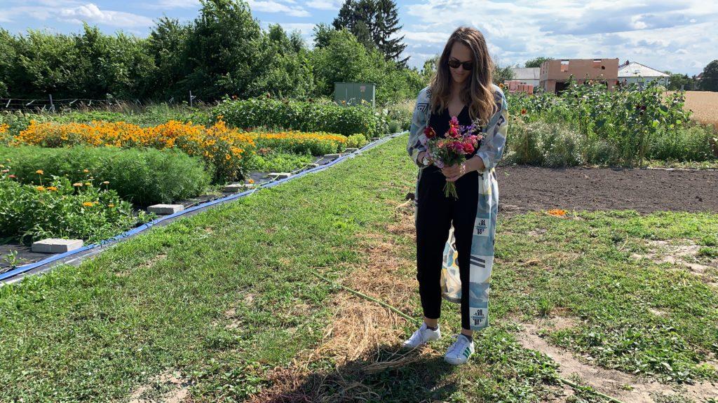 Auf dem Bild sieht man Visionistas Co-Geschäftsführerin Anna Oberdorfer mitten im Blumenfeld stehen. Sie hält einen bunten Blumenstrauß in der hand.