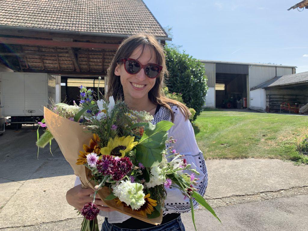 Auf dem Foto steht Katharina Reckendorfer, Gründerin von Blumenbund mit zwei großen Blumensträußen in der Hand am Hof ihrer Eltern im Weinviertel und strahlt in die Kamera.