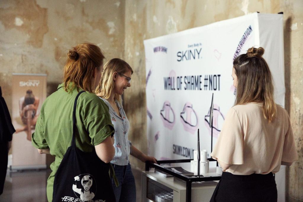 Auf diesem Bild sieht man drei Frauen die sich unterhalten und beim SKINY-Stand am Every Body In Festival stehen.