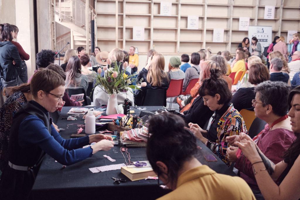 Auf diesem Bild sieht man Menschen, die an einem Tisch zusammen sitzen und an Craftivism Workshop von LUSH teilnehmen.