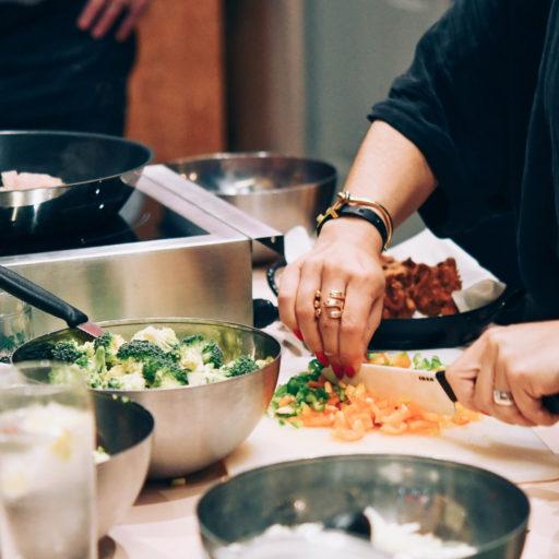 Eine Hand schneidet gerade Gemüse in einer Küche und ganz viele Schüssel sind schon mit unterschiedlichen geschnippelten Zutaten gefüllt
