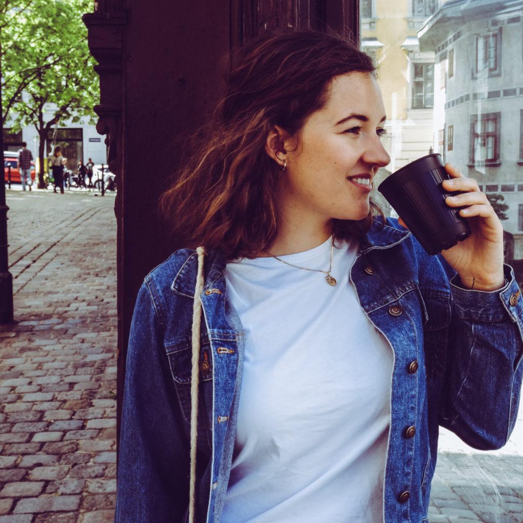 Auf diesem Bild sieht man eine Frau, die gerade aus einem myCoffeeCup Becher trinkt