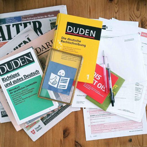 Wörterbücher, Dokumente und Zeitungen liegen auf einen Tisch. Auf ihnen die Kennzeichnung für Dokumente in Leichter Sprache.