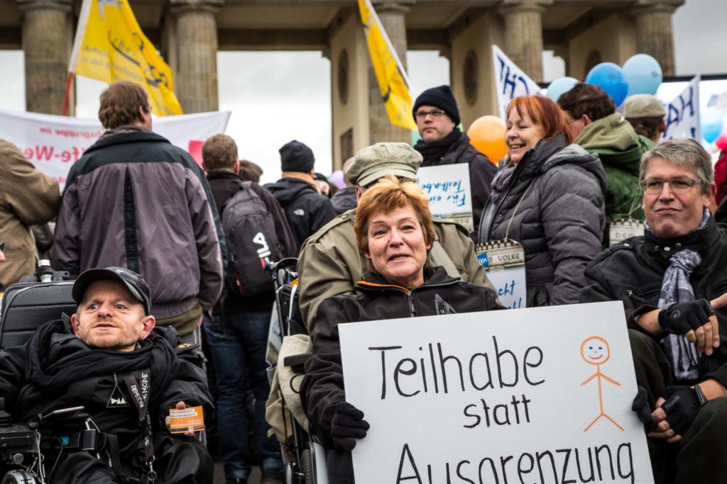 """Eine Demonstration am Potsdamer Platz. Viele Menschen mit Fahnen und Schildern. Vorne im Bild eine Frau im und zwei Männer im Rollstuhl. Die Frau hat in ihren Händen ein Schild: """"Teilhabe statt Ausgrenzung""""."""