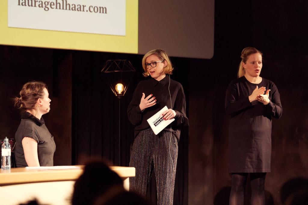 Auf diesem Bild sieht man Barbara Haas wie sie der Keynotespeakerin Laura Gehlhaar nach deren Präsentation eine Frage stellt. Daneben steht eine Frau und übersetzt in die Österreichische Gebrärdensprache.