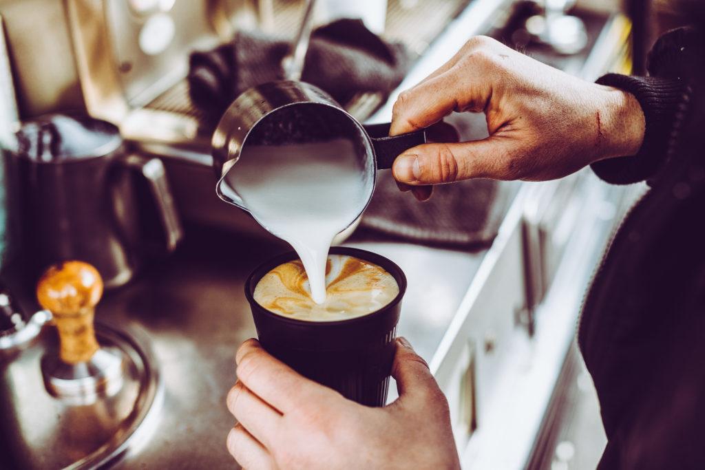 Auf diesem Bild sieht man, wie jemand einen Milchkaffee einschenkt