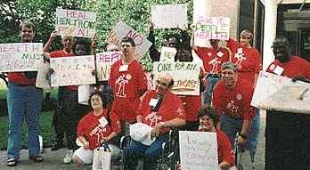 Das Bild zeigt eine Gruppe von Menschen. Sie tragen alle rote T-Shirts und Schilder. In der Mitte ein Mann im Rollstuhl. Fast alle Schilder sind unlesbar. Die Gruppe demonstriert für eine Gesundheits-System für alle.
