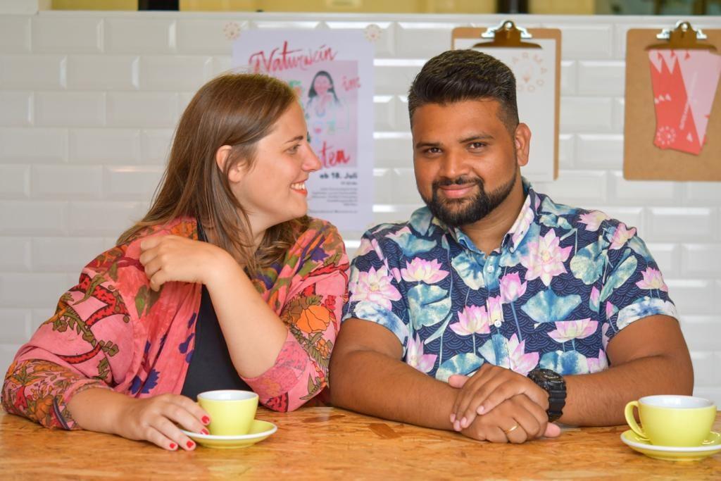 Auf dem Foto sind Simone und Adi Raihmann zu sehen, wie sie an einem Tisch sitzen und ein Heißgetränk zu sich nehmen.