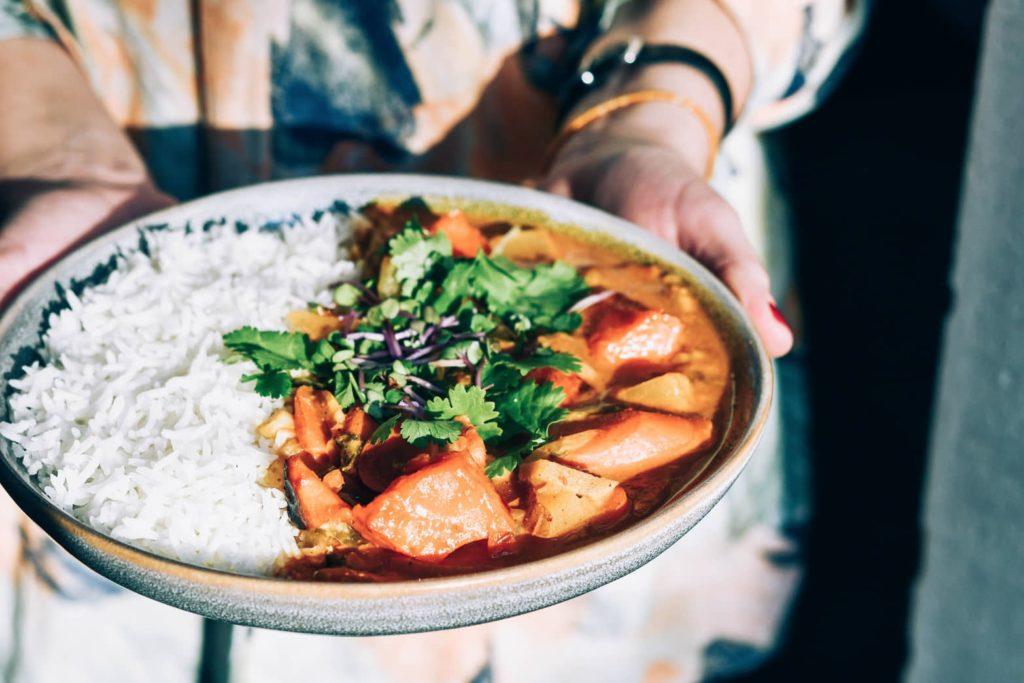 Auf dem Bild ist Veganes Curry auf einem Teller mit Reis zu sehen.