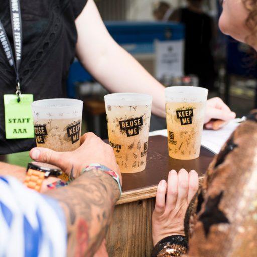 Wiederverwendbare Becher an einer Bar auf einem Festival. Der Kellner steht hinter der Theke. Zwei Festivalgäste davor.