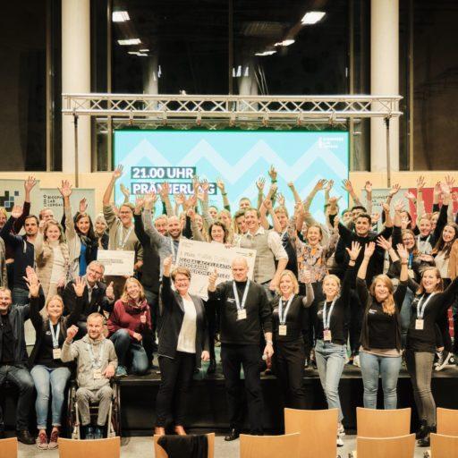 Auf dem Bild sind viele Personen vom Creators Camp for global ideas auf einer Bühne zu sehen. Die Leute halten alle ihre Hande in die Höhe.