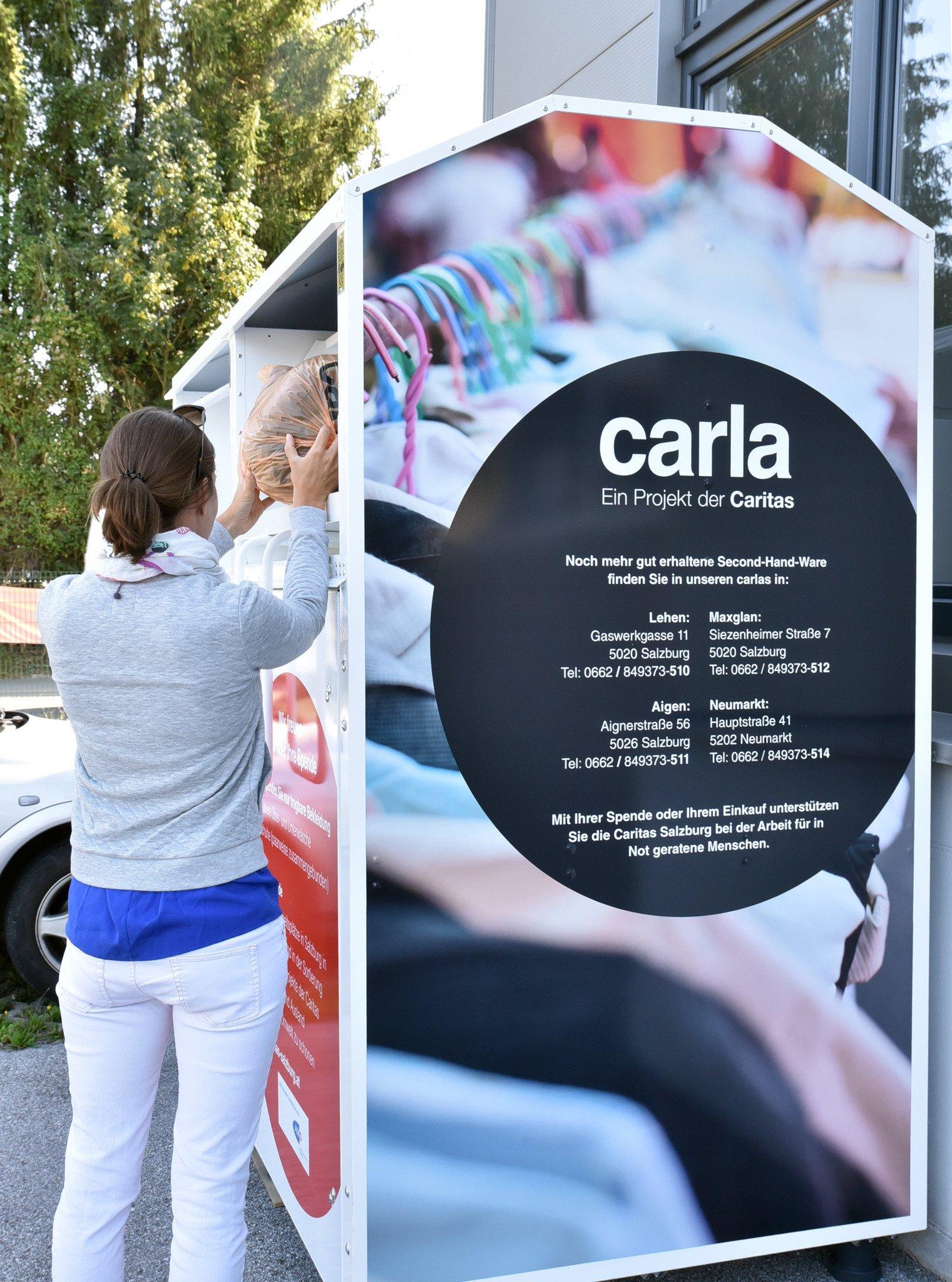 Auf diesem Bild sieht man eine Frau, die gerade Altkleidung in einen Sammelcontainer der carla wirft.