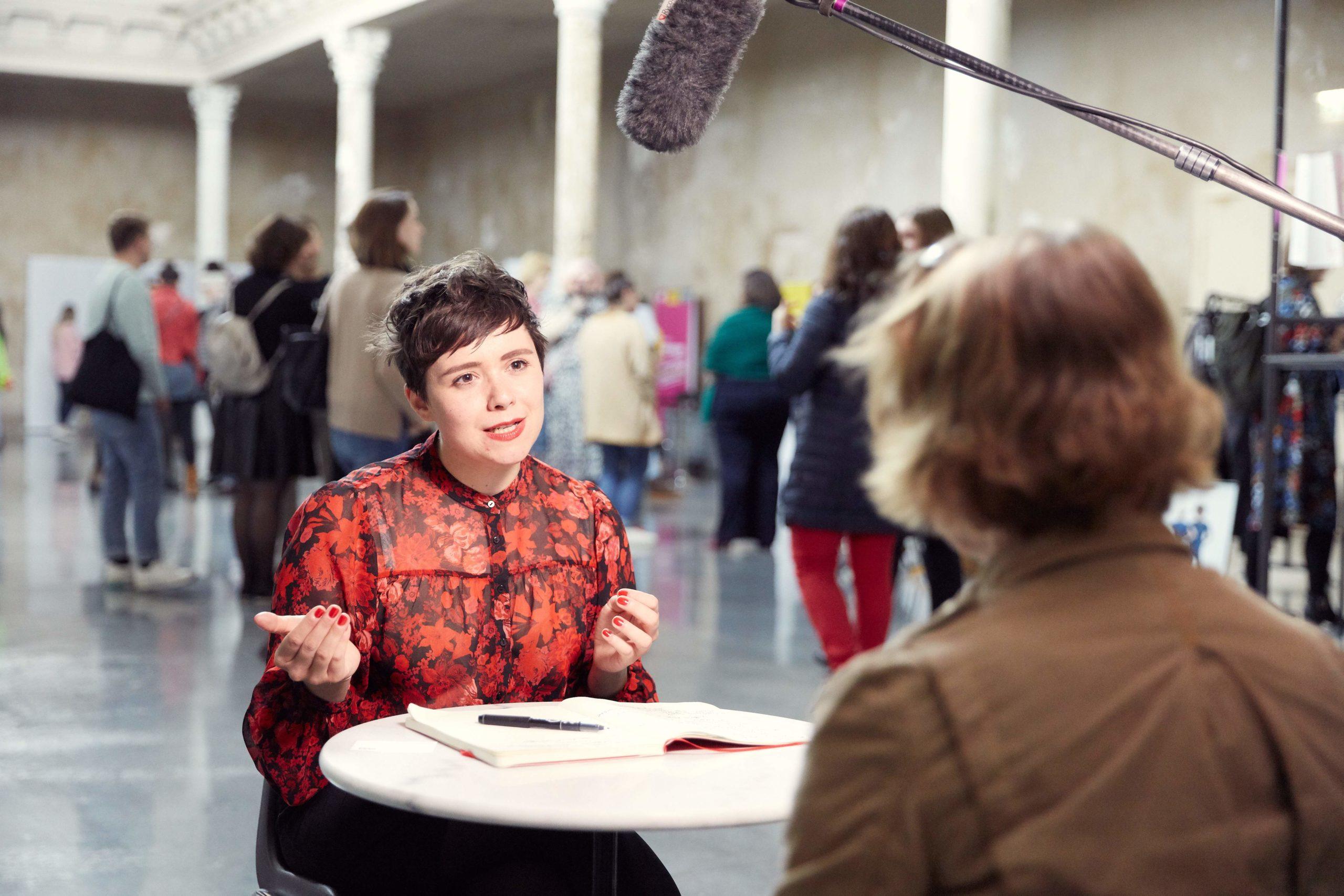 Auf diesem Bild sieht man eine junge Frau, die bei einem Tisch sitzt und ein Interview gibt.