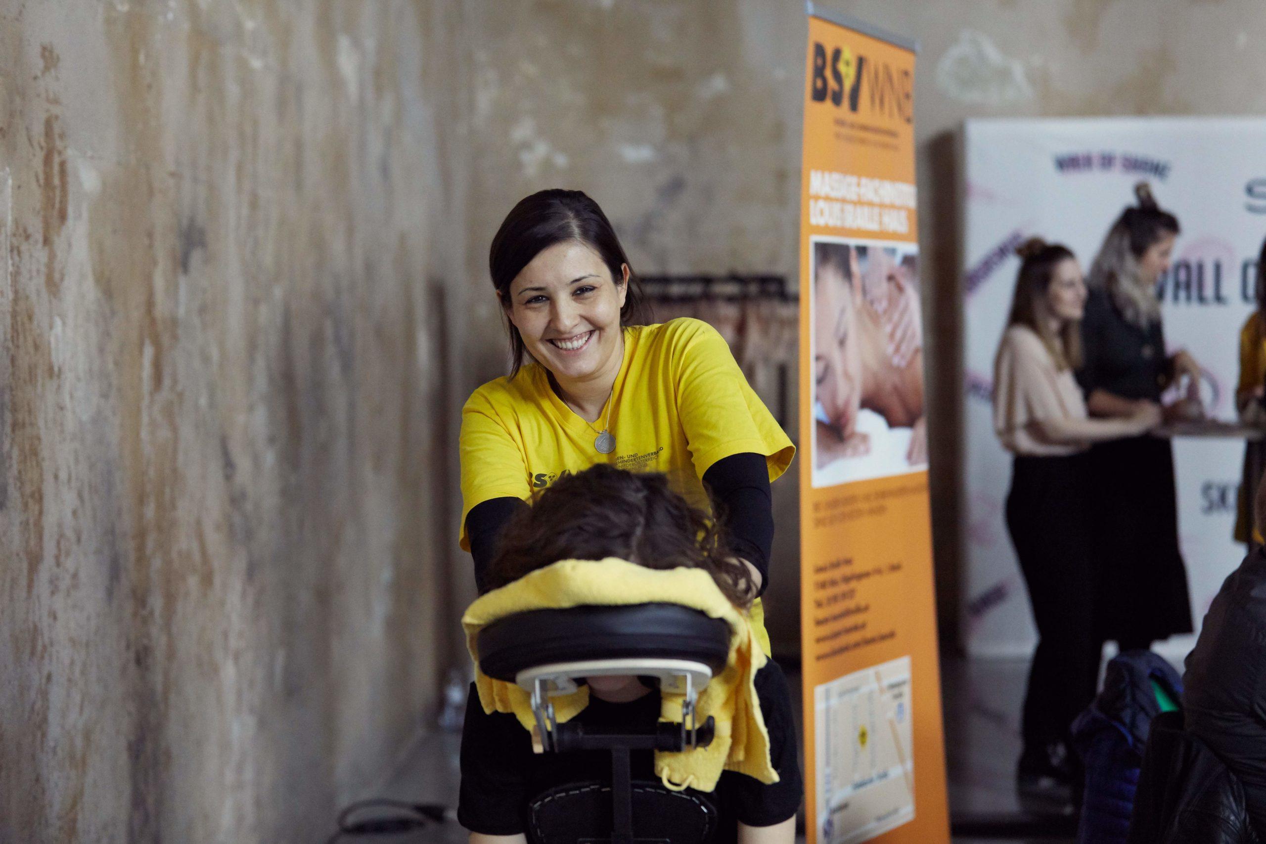 Auf diesem Bild sieht man eine junge Frau vom Blindenvberband, die gerade jemanden am Rücken massiert.