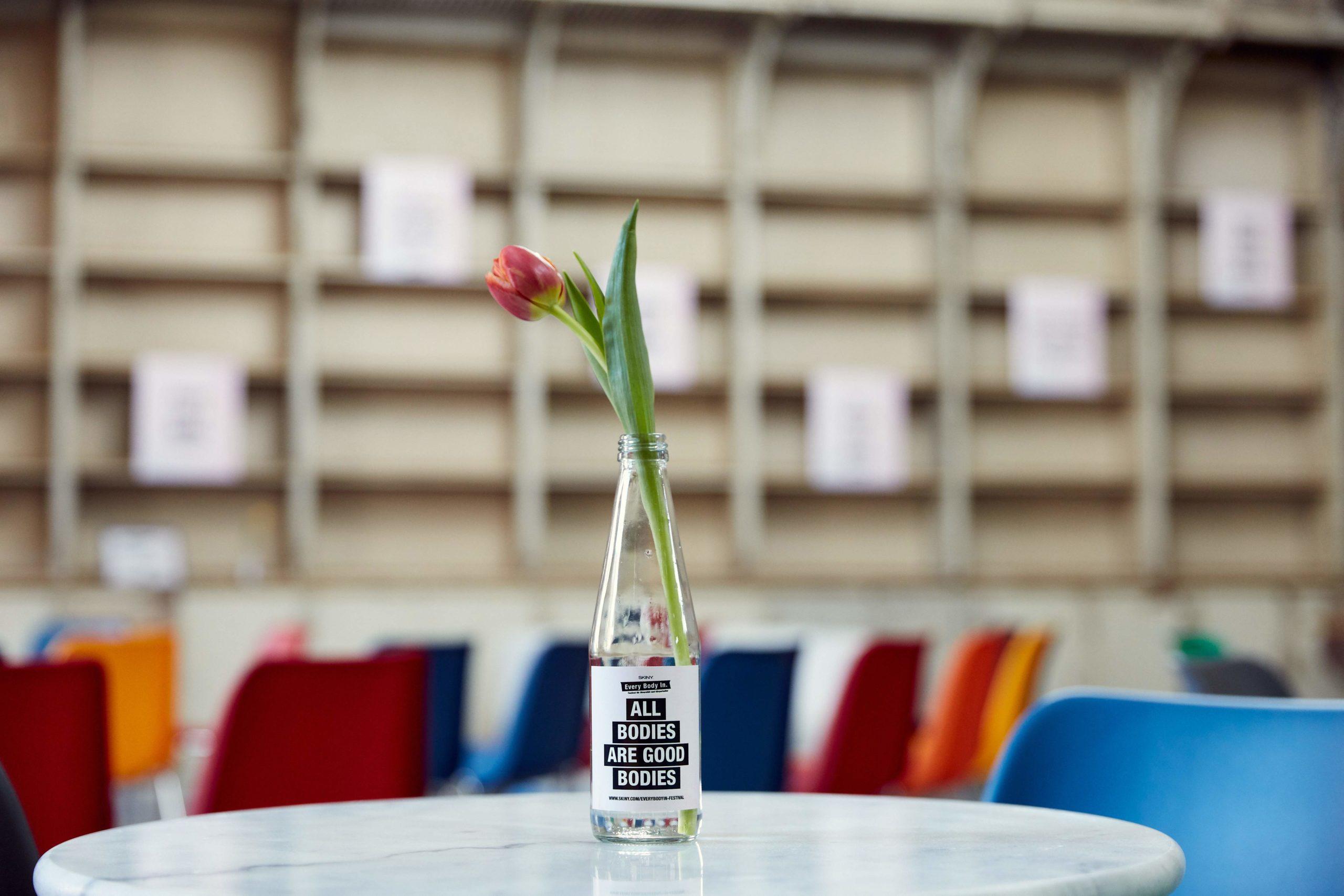 Auf diesem Bild sieht man eine Tulpe in einer Glasflasche auf einem Kaffeehaustisch. Auf der Glasflasche steht die Aufschrift: All bodies are good bodies.
