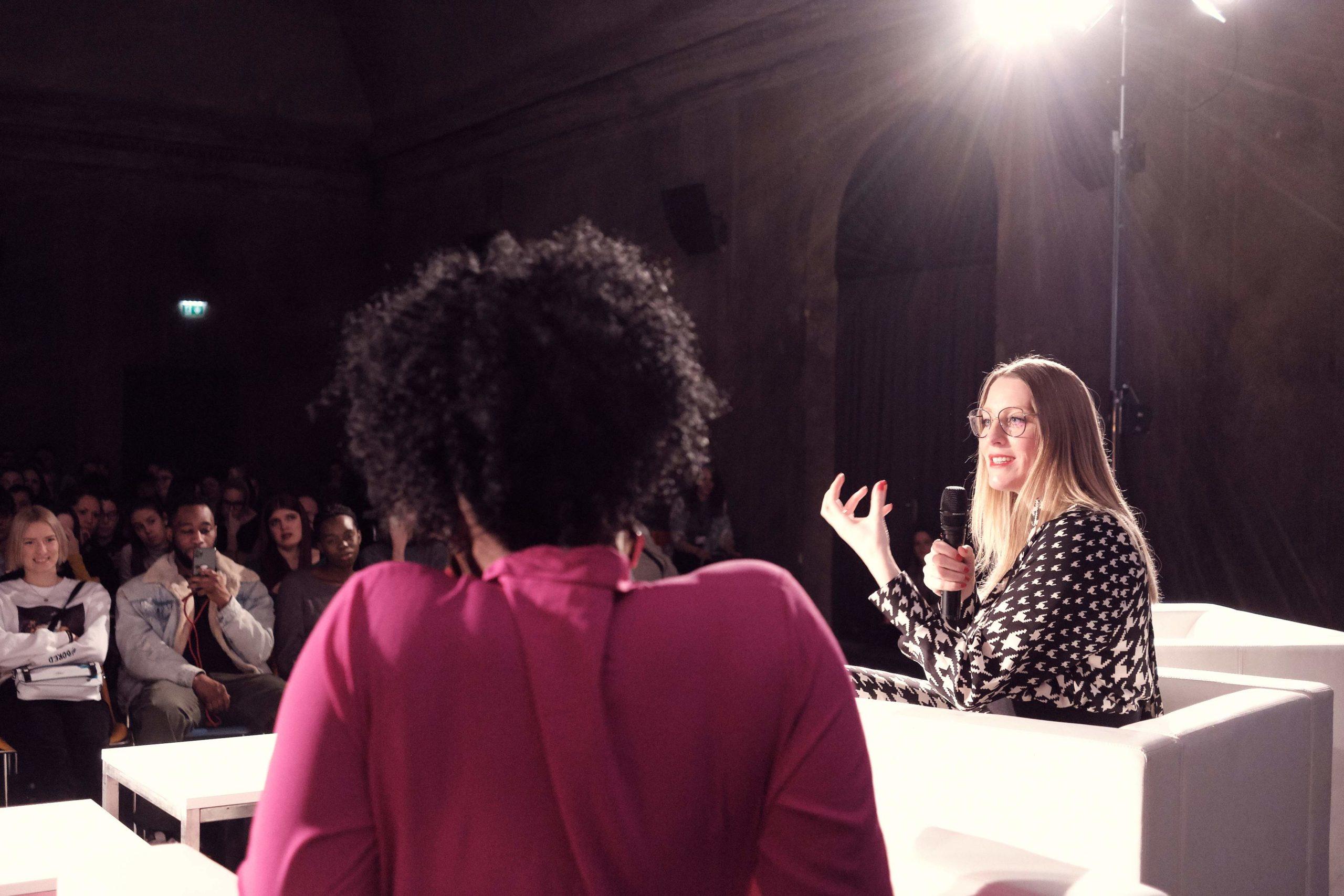 Auf dem Bild sieht man zwei Frauen, die auf einer Bühne am Podium diskutieren.