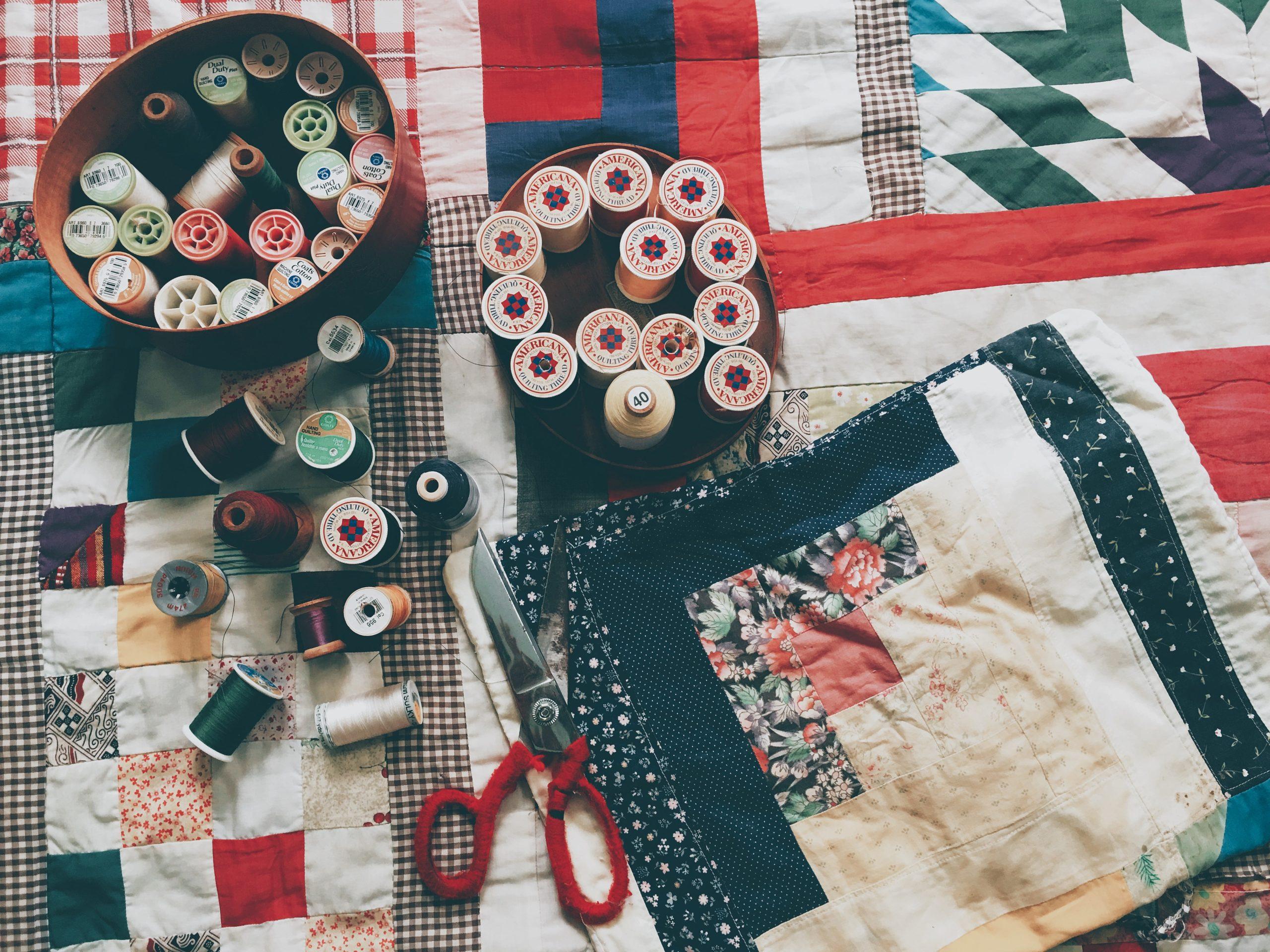 Auf diesem Bild sieht man Stoffe, Nadeln und Faden und eine Schere.