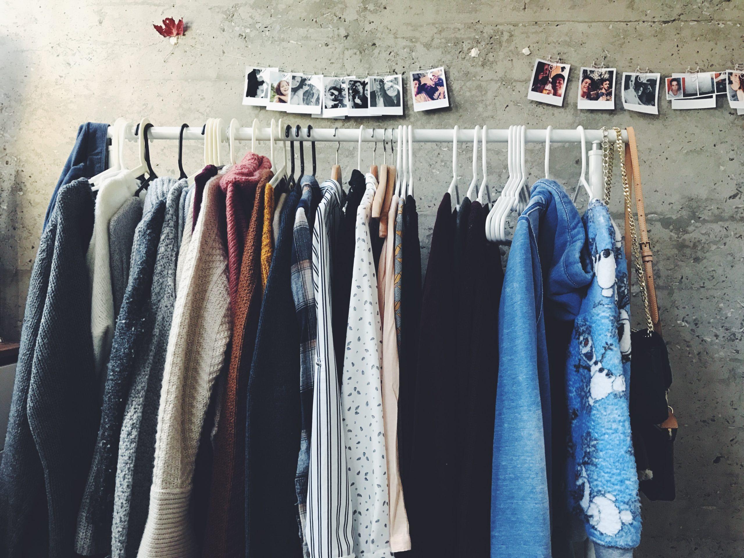 Auf diesem Bild sieht man eine Kleiderstange mit verschiedenen Kleidungsstücken.