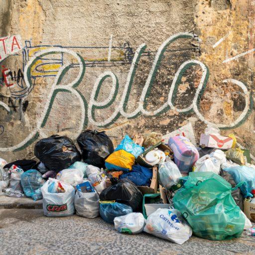 """Auf diesem Bild sieht man einen Müllberg und im Hintergrund den Schritzug """"La vita e bella"""""""