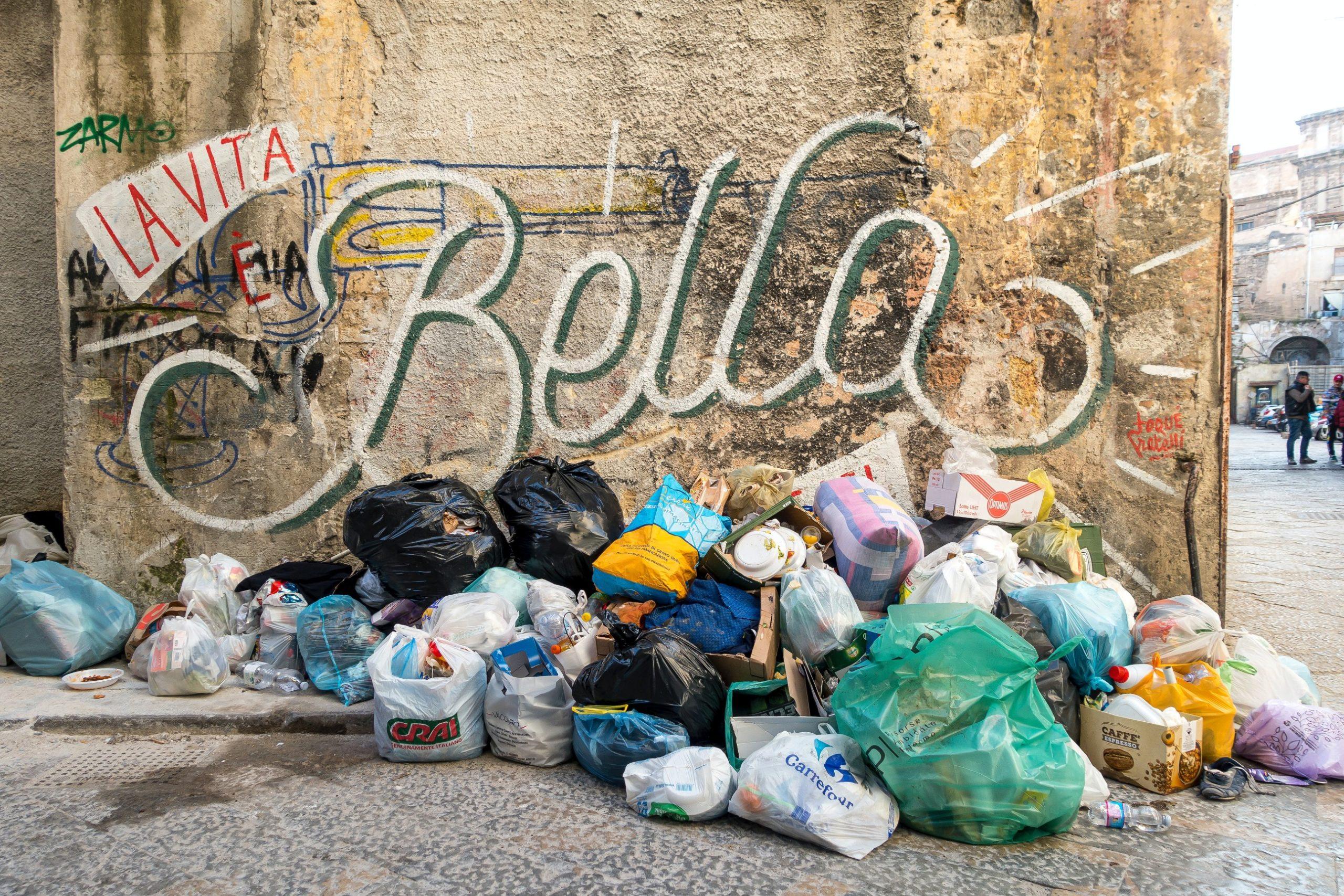 """Auf diesem Bild sieht man einen Müllberg und im Hintergrund den Schritzug """"La vita e bella""""."""