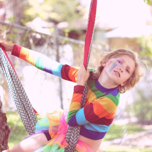 Ein Kind in Regenbogenpullover spielt an einen Baum auf einer bunten Hängematte. Im Gesicht ein Regenbogen.