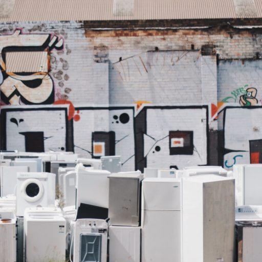 Auf diesem Bild sieht man einen Schrottplatz mit vielen Kühlschränken, Waschmaschinen & Co.