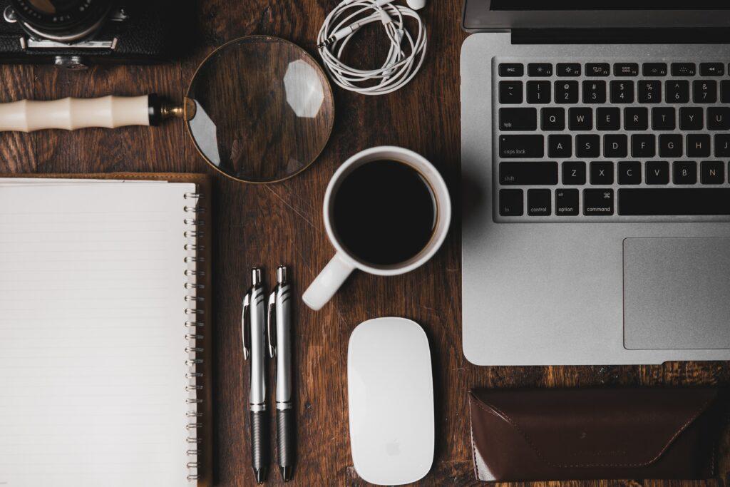 Auf diesem Bild ist ein Schreibtisch mit Computer, Kaffee und Notizblock zu sehen.